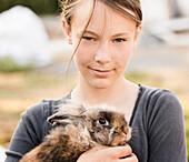 Serious girl holding rabbit on farm