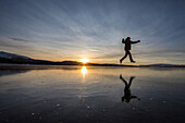 Hiker jumps on the frozen surface of Lake Limingen, Rorvik, Borgefjell National Park, Trondelag, Norway, Scandinavia, Europe