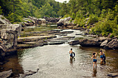 Three young women hike and play in the water at Little River Canyon National Reserve.