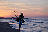 Man waking on the beach with his kitesurfing equipement.
