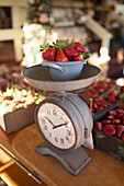 In a fruit stall strawberries are put on a weighing scale.