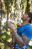 A father and his son reach for a climbing rope while looking up at a climbing route.