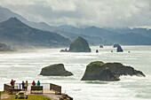 Tourists enjoy the view of Haystack Rock and Cannon Beach looking south from a viewpoint in Ecola State Park, Oregon.