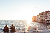 Two young women on a seawall at sunset, Rovinj, Istria, Croatia