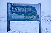 Place name sign of Tuktoyaktuk in wintertime, Inuvik region, Northwest Territories, Canada