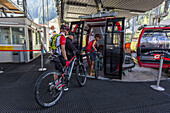 Couple pushing their mountain bikes into a cable car at Ciampioni station, Wolkenstein, Trentino South Tyrol, Italy