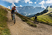 Mountain biker couple at the Ciampinoi, behind it Sella Group, Trentino South Tyrol, Italy