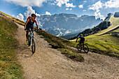 Mountainbiker Paar am Ciampioni, dahinter Sella Gruppe, Trentino-Südtirol, Italien