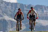 Mountain biker couple at Ciampinoi, behind it Sella Group, Trentino South Tyrol, Italy