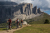 Mountain bikers in the Langkofel area behind it Sella group, Trentino South Tyrol, Italy