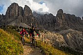 Mountain biker at Gardena Pass, Sella group in the background, Trentino, South Tyrol, Italy