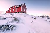 Pink sky on the typical red house of fishermen rorbu, Henningsvaer, Lofoten Islands, Arctic, Northern Norway, Scandinavia, Europe
