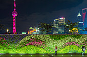 Vegetal wall on the Bund and view over Pudong financial district skyline at night, Shanghai, China, Asia