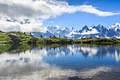 Low clouds and mist around Grandes Jorasses and Mont Blanc while hikers proceed on Lac De Cheserys, Haute Savoie, French Alps, France, Europe