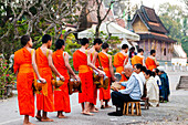 Monks recieving morning alms and Xieng Thong Monastery in the background, Luang Prabang, Laos, Indochina, Southeast Asia, Asia