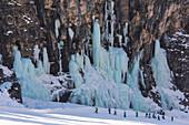 Skiers underneath the frozen waterfall, Hidden Valley ski area, Lagazuoi, Armentarola 101, Ski piste, Dolomites, UNESCO World Heritage Site, South Tyrol, Italy, Europe