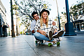 Caucasian couple riding skateboard