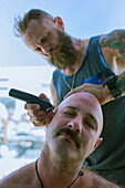 Caucasian man shaving head of friend