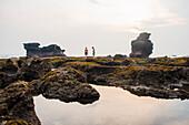 Caucasian children exploring rocky tidal pools, Canggu, Bali, Indonesia