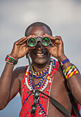 Black man in traditional clothing using binoculars