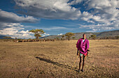 Black man in traditional clothing standing in remote field