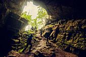 Hikers exploring rock cave