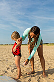 Mother spraying sunscreen on daughter at beach