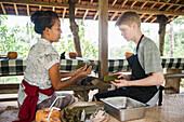 Chef training teenage boy in outdoor kitchen