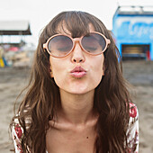 Caucasian woman in sunglasses puckering to kiss at beach