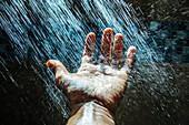 Caucasian man rinsing hand under water