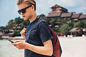 Caucasian man using cell phone on beach