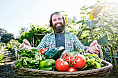 Caucasian man holding basket of vegetables in garden