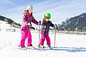 boy and girl skiing on the slope, Pfronten, Allgaeu, Bavaria, Germany