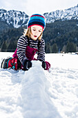boy forming snowballs in winter, Pfronten, Allgaeu, Bavaria, Germany