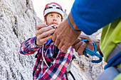 Climber handing over carabiners on the Herzogkante, Laliderer Northface, Lalidererspitze, Hinterriss, Ahornboden, Karwendel, Bavaria, Germany