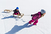 Girl pulling boy on his sled, Pfronten, Allgaeu, Bavaria, Germany