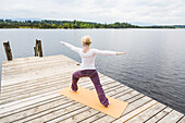 woman doing Yoga on the jetty, sun salute, Kirchsee, Bad Toelz, Bavaria, Germany