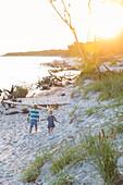 Children walking along the beach at sunset, dream beach between Strandmarken und Dueodde, adventure, sandy beach, summer, Baltic sea, Bornholm, Strandmarken, Denmark, Europe