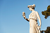 Statue of female figure against a blue sky, Rome, Italy
