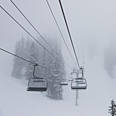 Empty chairlift at a ski resort in fog, Whistler, British Columbia, Canada