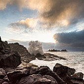 Glowing clouds at sunset with waves crashing against the rocks, Tofino, British Columbia, Canada