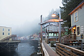 The Creek Street sign and boardwalk in the fog, downtown Ketchikan, Southeast Alaska, USA, Spring