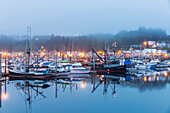 Boats in Ketchikan Harbor reflecting on the calm ocean waters on a foggy night, Ketchikan, Southeast Alaska
