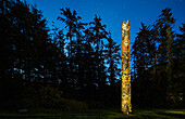 A large Totem Pole lit up at night in Sitka National Historic Park, Sitka, Southeast Alaska, USA, Summer