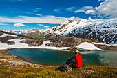 Hiker rests alongside a lake while hiking the Harding Icefield Trail, Kenai Fjords National Park, Kenai Peninsula, Southcentral Alaska
