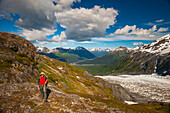 A man hiking near the Harding Icefield Trail with the Chugach Mountains and the Resurrection Valley in the background, Kenai Fjords National Park, Southcentral Alaska