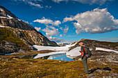 Man hiking alongside a lake while hiking the Harding Icefield Trail, Kenai Fjords National Park, Kenai Peninsula, Southcentral Alaska