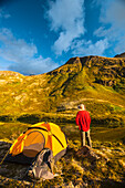 A man at his campsite at Hanging Valley in South Fork near Eagle River on a summer day in South Central Alaska.