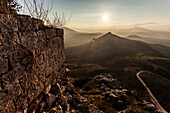 Ruins of a stone wall with a sunburst and mountains, Corinth, Greece