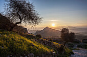 Sun setting over the peaks of mountains, Corinth, Greece
